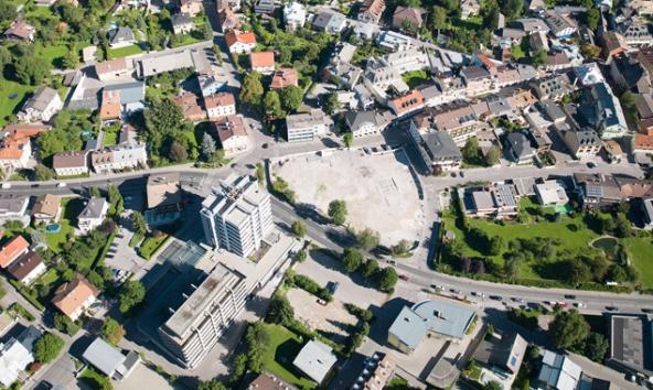 Schräg gegenüber des Dolomitenhotels soll dort, wo jetzt die kleine Grünfläche ist, die zweite Rampe aus der Kaufhausgarage führen. Auf dem Lugger-Luftbild gut zu sehen ist auch der geförderte Bauplatz südlich der Bundesstraße. Hier soll unter anderem ein Hotel Platz finden.