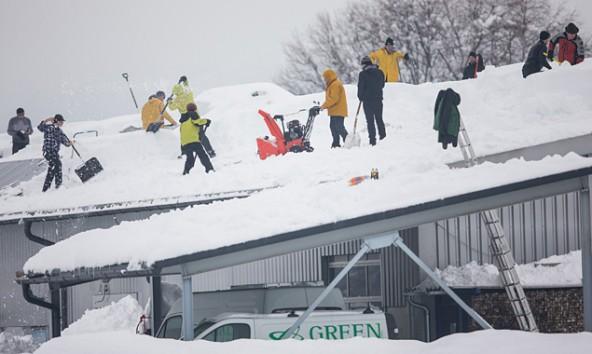 Mitarbeiter und Helfer schaufeln das Dach einer Eletrofirma in Osttirol frei. Der Schnee ist schwer geworden. Foto: Expa/Groder
