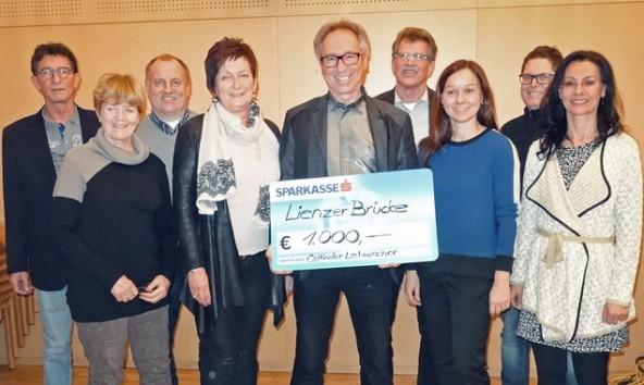 """Andreas Weiskopf hält einen großen Scheck über 1000 Euro in Händen, gespendet vom Osttiroler Lehrerchor und der Band """"Jazz we  can""""."""