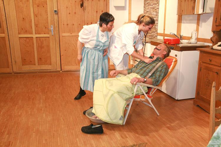 äuerin Maridl (Ingrid Kleinlercher) und Krankenschwester Christl (Carina Kofler) kümmern sich um den kranken Hausherren Franz (Ludwig Zathamer).
