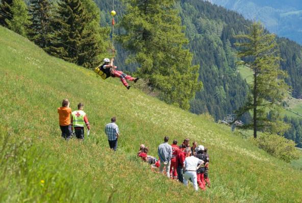 Aus der Luft schwebt Rettung ein. Der Gleitschirmpilot wird mittels Seil geborgen. Foto: Brunner Images