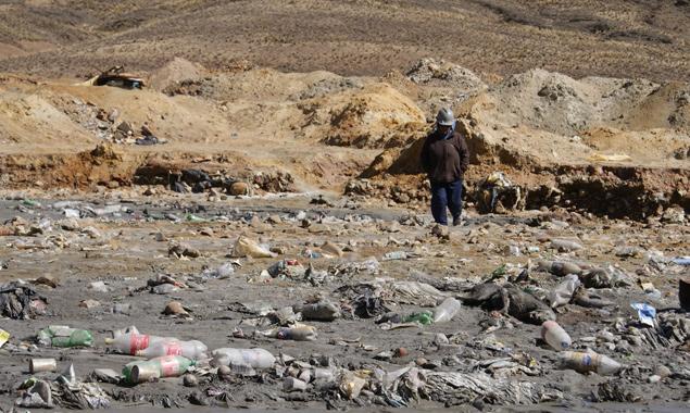 Nahe einem Bergwerk in Bolivien: Müll vermischt sich mit giftigen Abwässern, dennoch versuchen Menschen, daraus wertvolle Mineralien zu filtern.
