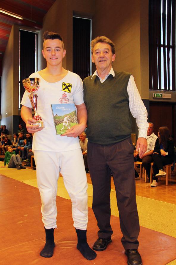 """Philip Holzer wurde mit dem schönsten Wurf des Turniers von Günther Heim mit dem Buch ,,Mythos Hundstoan"""" ausgezeichnet"""