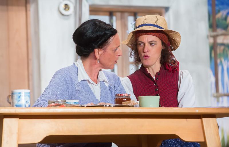 Auch ein bisserl Tratsch gehört zum Leben am Hof der Brunner-Bauern im Stück, v.l.: Sabine Hopfgartner (als Bäuerin Emma) und Monika Linder (als Kräuterliesl)